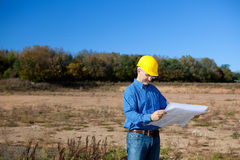 Architect Holding Blueprint On Construction Site Stock Photo
