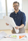Architect Holding Blueprint At Desk In Office Royalty Free Stock Photography