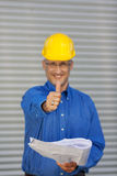 Architect Holding Blueprint While Gesturing Thumbs Up Stock Photo
