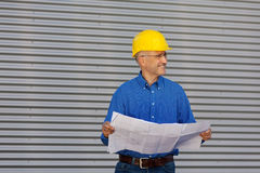 Architect Holding Blueprint While Looking Away Against Shutter Royalty Free Stock Photo