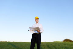 Architect Holding Blueprint While Looking Away On Field Against Stock Photography