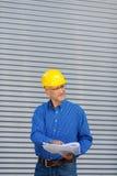 Architect Holding Blueprint While Looking Away Stock Photo