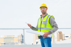 Architect holding blueprints and clipboard outdoors Stock Photography
