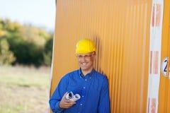 Architect Holding Blueprints While Leaning On Trailer Stock Image