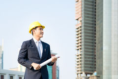 Architect holding blueprints and looking at the building at the Royalty Free Stock Photography