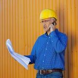 Architect Holding Blueprints While Using Mobile Phone Royalty Free Stock Photo