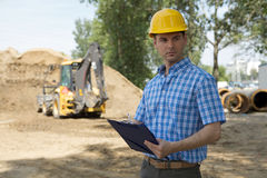 Architect holding clipboard at construction site, bulldozer in background Stock Image