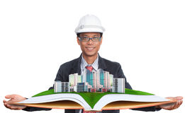 Architect holding green field with modern building above Stock Images
