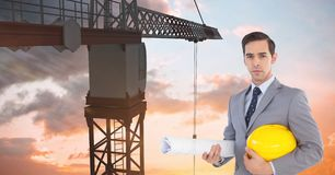Architect holding hardhat and blueprint in front of crane Royalty Free Stock Image