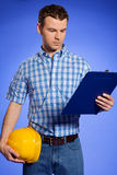 Architect holding hardhat and looking at clipboard Royalty Free Stock Photos