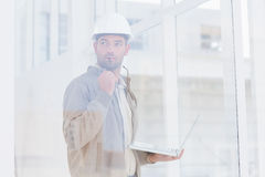 Architect holding laptop while looking away in office Stock Images