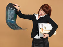 Architect holding laptop, papers,. Portrait of a bussy, young woman architect, holding a laptop and a blueprint, talking on the telephone, on beige background royalty free stock photos