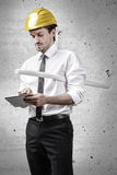 Architect holding a plan and working on a touchpad Royalty Free Stock Photography