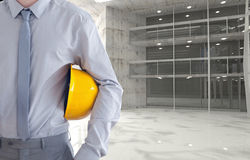 architect holding yellow safety helmet against room background Royalty Free Stock Photo