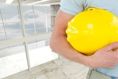 Architect holding a yellow safety helmet against room background Royalty Free Stock Photos