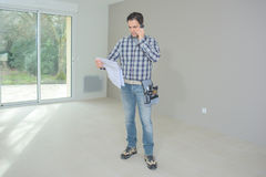 Architect inspecting blueprint while at construction site Stock Image