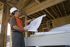 Architect Inspecting At Construction Site. Architect with blueprint looking at framework in construction site Royalty Free Stock Photography