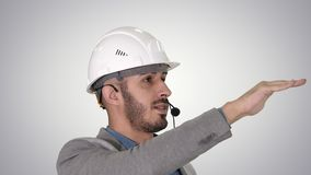 Architect inspects work of crane talking through head set, on gradient background. stock footage