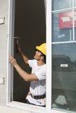 Architect Installing New Window. Male architect installing new window at construction site royalty free stock photography