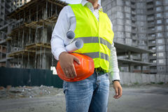 Architect in jacket posing with red helmet at construction site Stock Photos