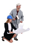 Architect kneeling by decorator Stock Image