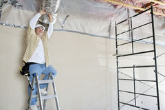 Architect on ladder working on ceiling royalty free stock image