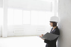 Architect Leaning Against Wall With File Folder In Warehouse Stock Photography