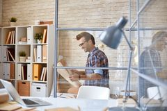 Architect learning draft. Handsome architect looking at unfolded blueprint in office Stock Photos