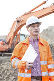 Architect looking away while holding clipboard at construction site Royalty Free Stock Photo