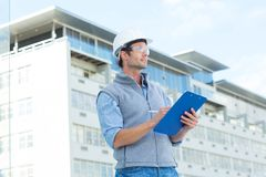 Architect looking away while writing on clipboard Stock Image