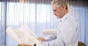 Architect looking at blueprint stock footage