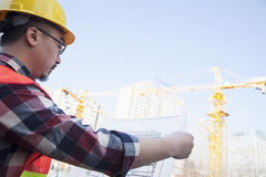 Architect looking at a blueprint outdoors at a construction site Stock Photo