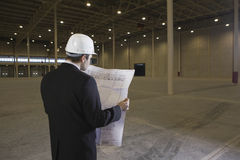 Architect Looking At Blueprint In Warehouse. Rear view of male architect looking at blueprint in empty warehouse Stock Photography