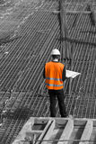 Architect looking at blueprints in a building site, selectve color Royalty Free Stock Photos