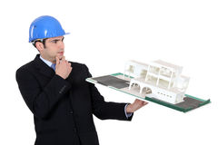 Architect looking at building. Architect considering a non-conventional model Stock Photo