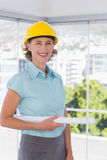 Architect looking at camera with helmet and blueprint Royalty Free Stock Images