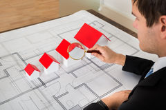 Architect Looking At House Models Through Magnifying Glass Royalty Free Stock Images