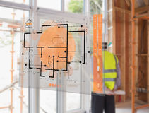 Architect looking out window with hologram interface in foreground Royalty Free Stock Image
