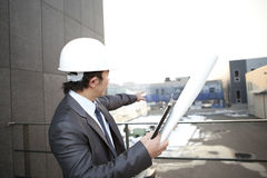 Architect looking and pointing building construction. Young architect with white helmet holding blueprint and clipboard pointing at the building construction Royalty Free Stock Photo