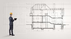 Architect looking to a house plan. Architect watching a 2 dimension house plan royalty free stock images