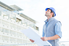 Architect looking up while holding blueprint Royalty Free Stock Images