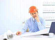 Architect looking working in office at desk. Royalty Free Stock Photography