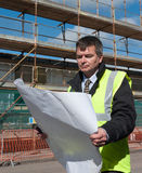 Architect looks down at plans. Architect or engineer at work on a building site. Looks down at plans of construction work. Concentrating Royalty Free Stock Images