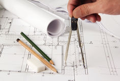 Architect making corrections on plans. Architect making corrections on architectural plans with a compass Stock Images