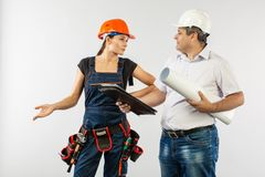 An architect man wearing a hard hat or helmet and co-worker builder woman reviewing blueprints stock photo