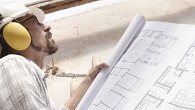 Architect man at work, wearing helmet and headphones looking at blueprint, check the construction house project plan, in