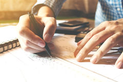 Architect man working with drawing compass on desk office room. Royalty Free Stock Images