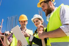 Architect of manager die aan haar collega's elektronisch de bouwplan tonen stock afbeeldingen