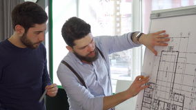 Architect moves his hand over the design of the building. Young male architect moving his hand over the design of the building. Close up of two brunette