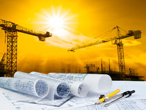 Architect Plan On Working Table With Crane And Building Construction Background Stock Photo
